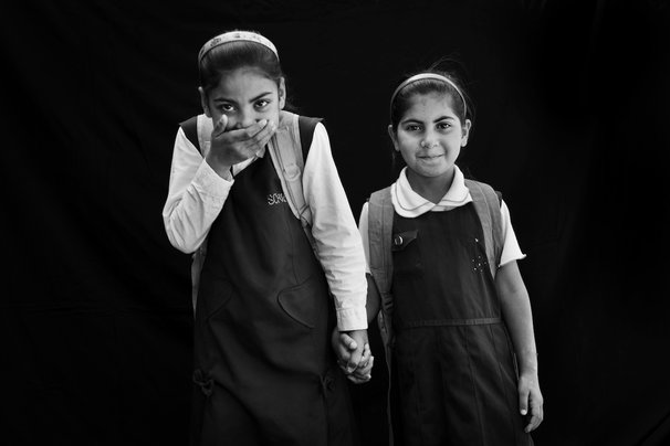 Aya Abbas Hussain, 9, left, and, Banee Adel Abdullah, 8, right, stand for a portrait in Baghdad, Iraq